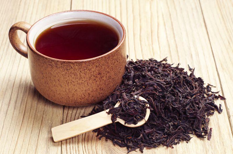 black tea leaves beside mug of black tea