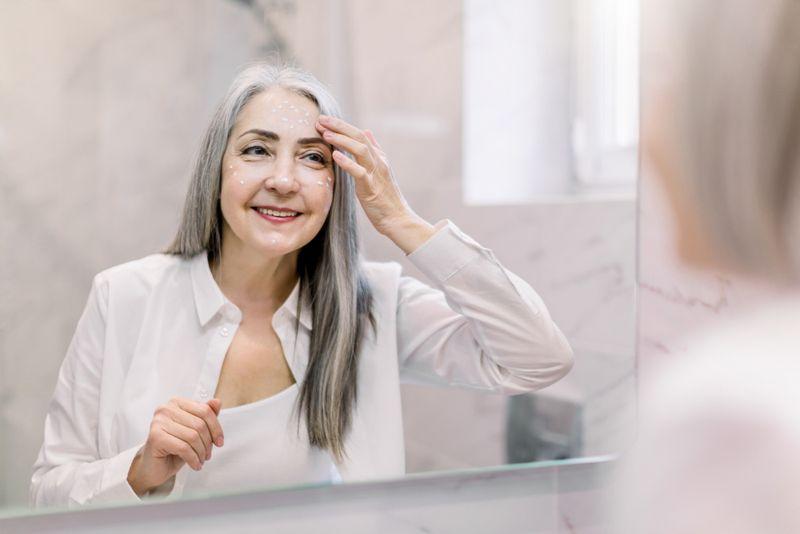 older woman applying skin cream in mirror