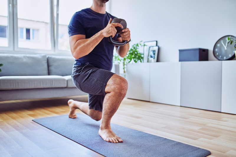 man doing lunges with a kettlebell
