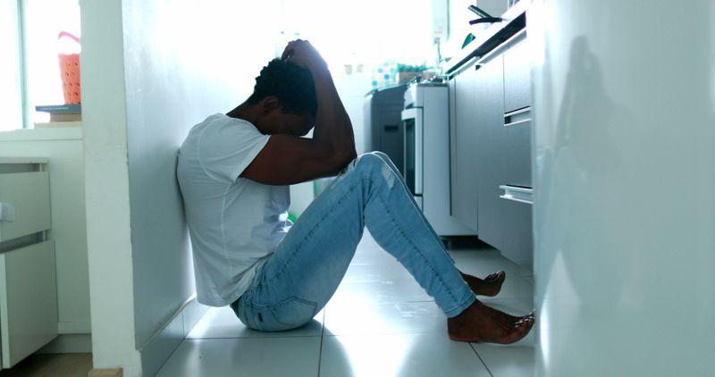depressed man sitting on kitchen floor