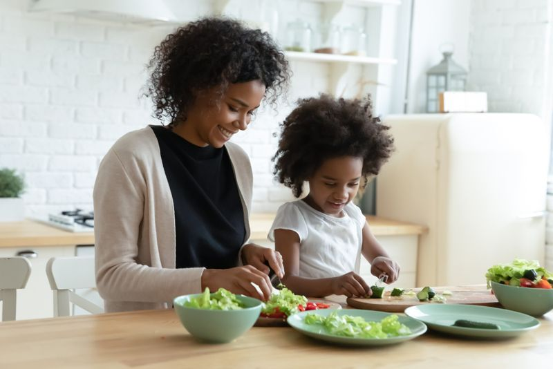 smiling mother and daughter making salads
