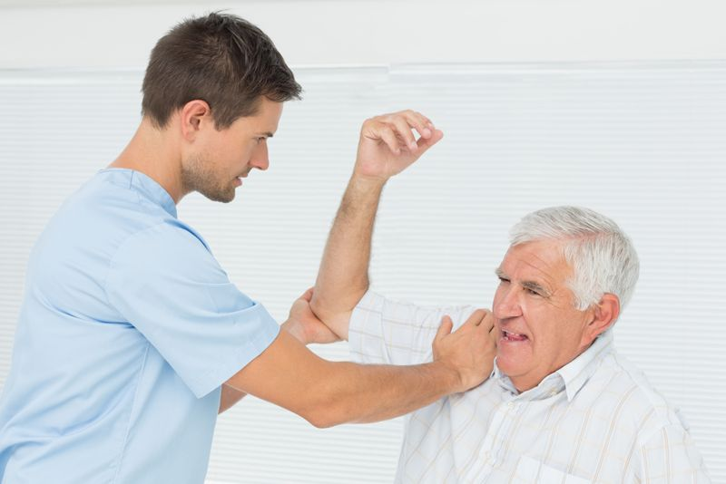 younger medical personnel helping older patient move shoulder