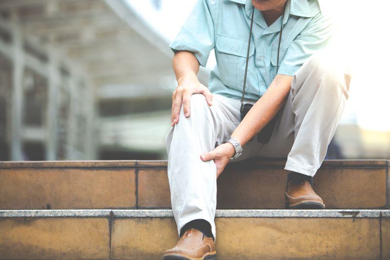 older man sitting on steps with sore leg