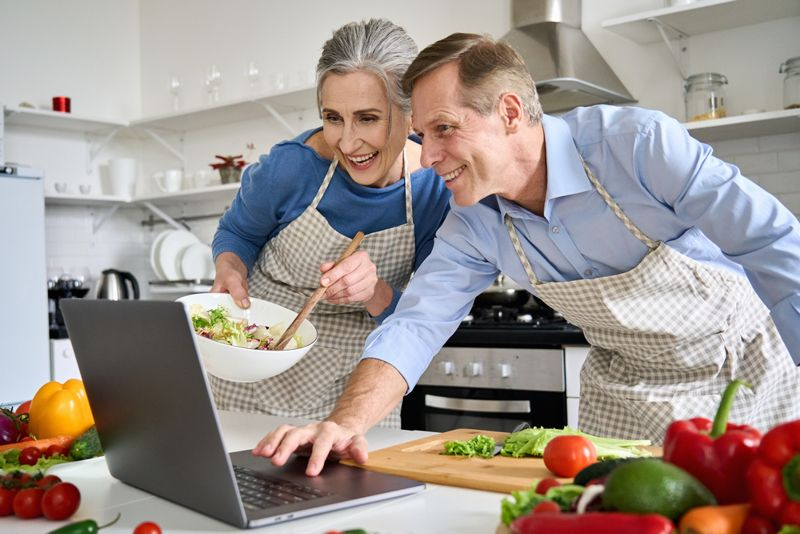 couple cooking with recipe on laptop