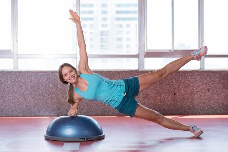 woman doing a side plank on a bosu ball