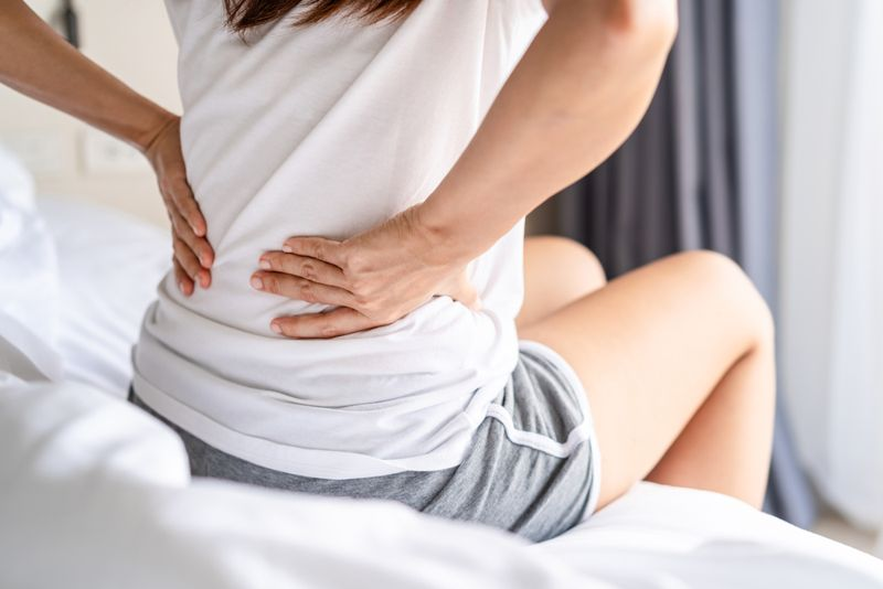 woman with sore back sitting on bed