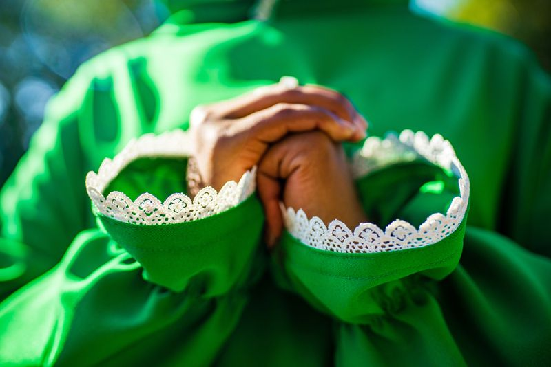 close up hands of muslim african american woman in green dress