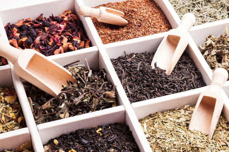 box of various loose teas with scoops