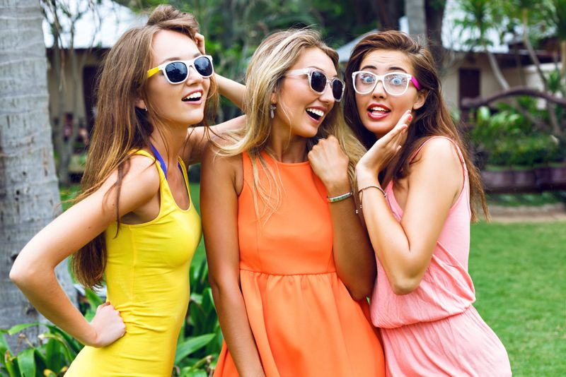 Close up outdoor fashion bright lifestyle portrait of three young pretty women wearing bright summer dresses and sunglasses.Whispering and gossip.
