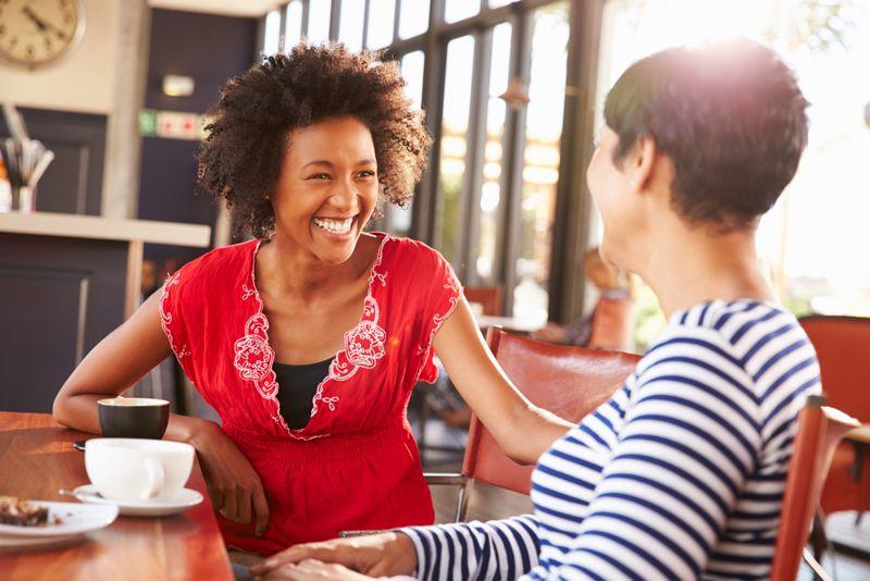 two women smiling, having coffee