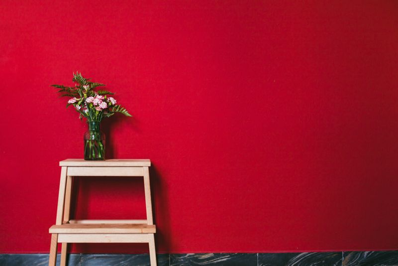 red wall with flowers against on bench