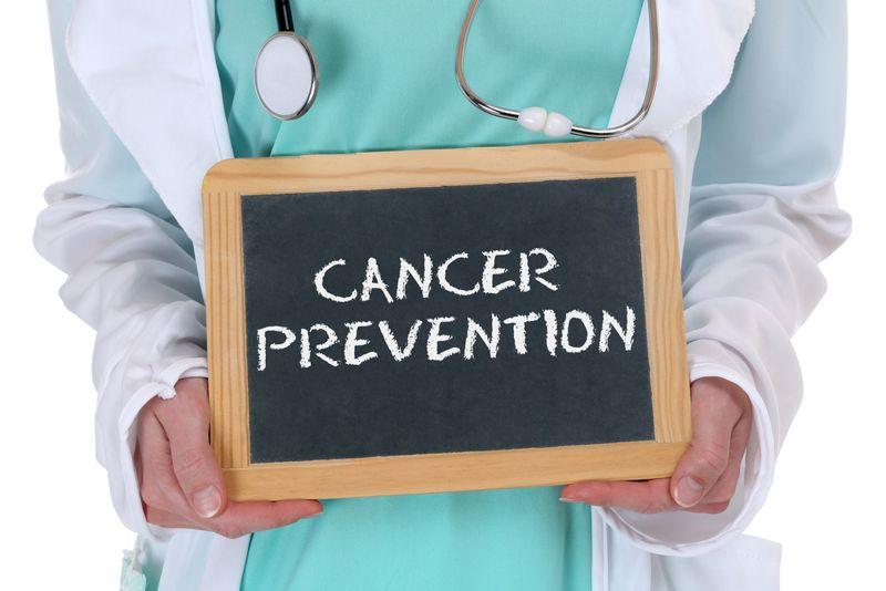 doctor holding chalkboard sign cancer prevention