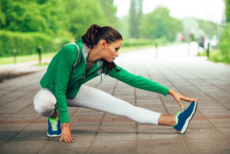 woman stretching her legs before running