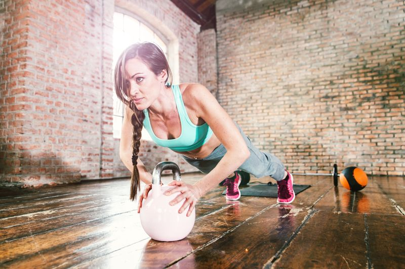 woman with kettlebell doing pushup workout
