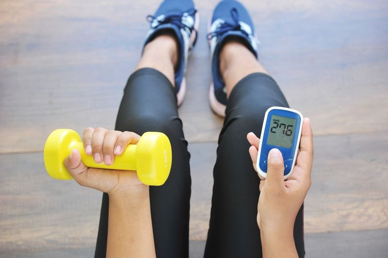 woman holding weight and blood sugar monitor
