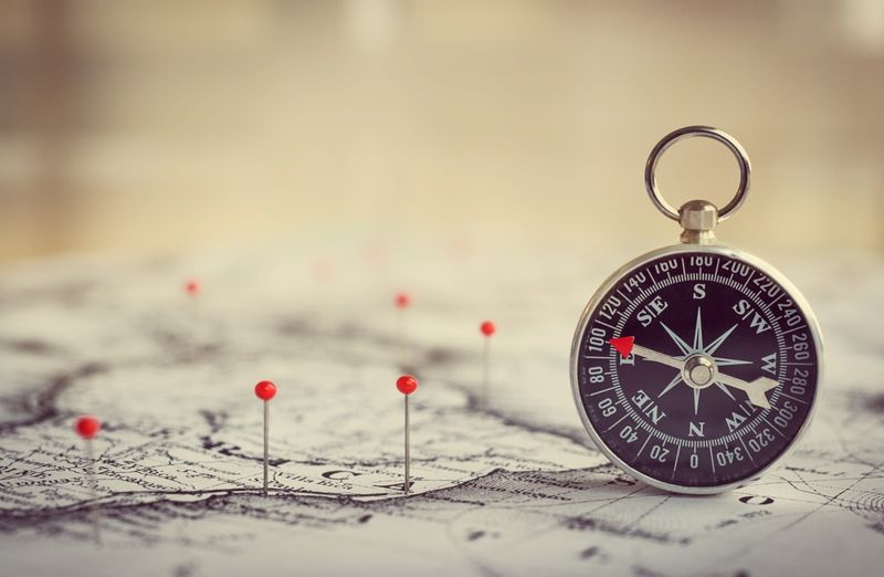compass sitting on a map with pins