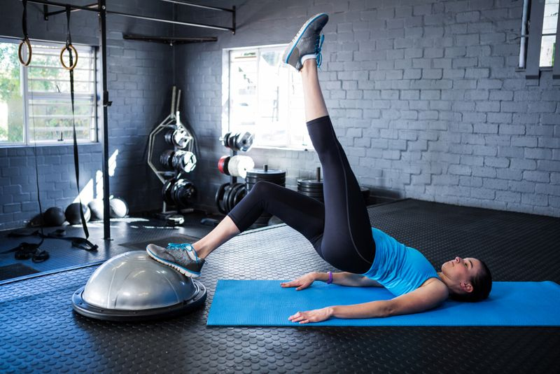 woman doing hip lifts on a bosu ball exercise