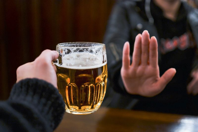 women saying no to offer of beer