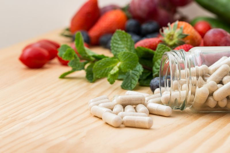 dietary supplement capsules on counter with vegetables