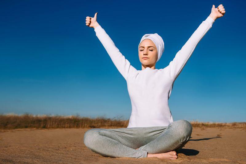 woman outside doing kundalini yoga breathing meditation