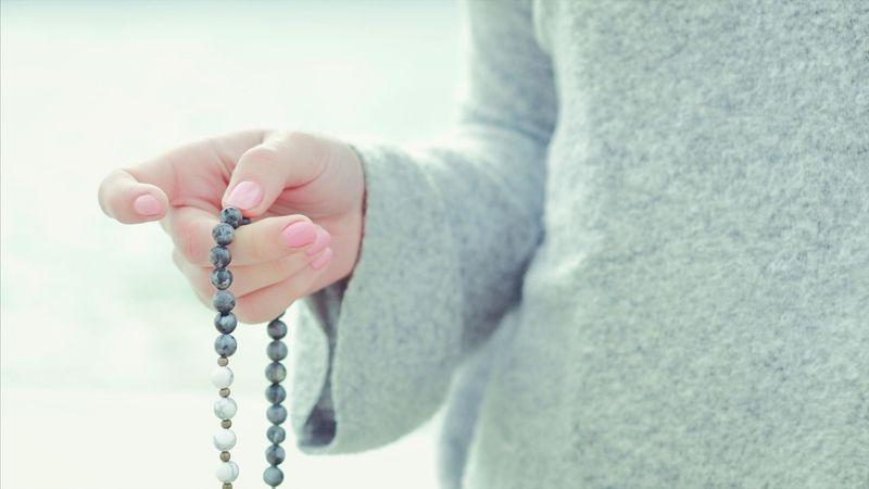 woman holding mala beads meditation concept