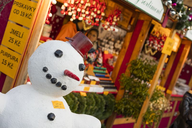 A snowman in fornt of the shops at the traditional Christmas markets at the Peace Square (Namesti Miru) in Prague, Czech republic.