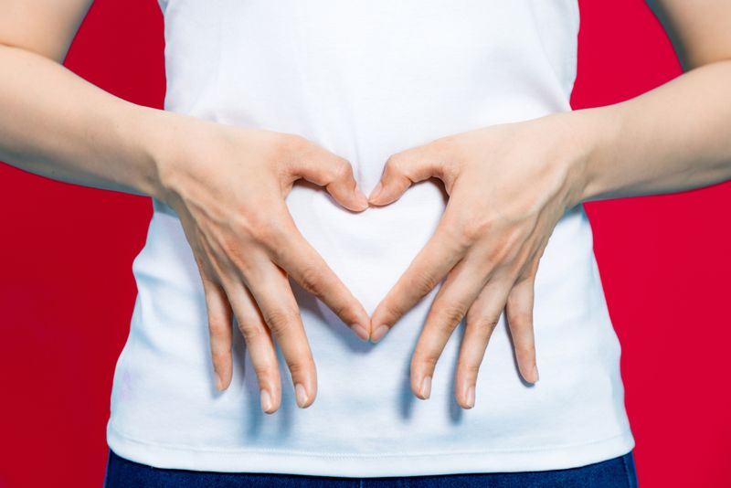 woman forming heart with fingers over stomach