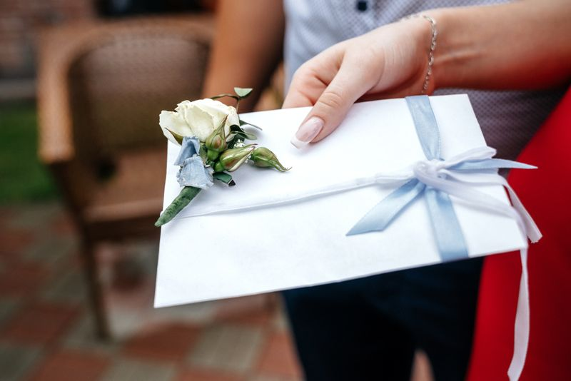 White wedding envelope with a boutonniere in the hand of a woman.