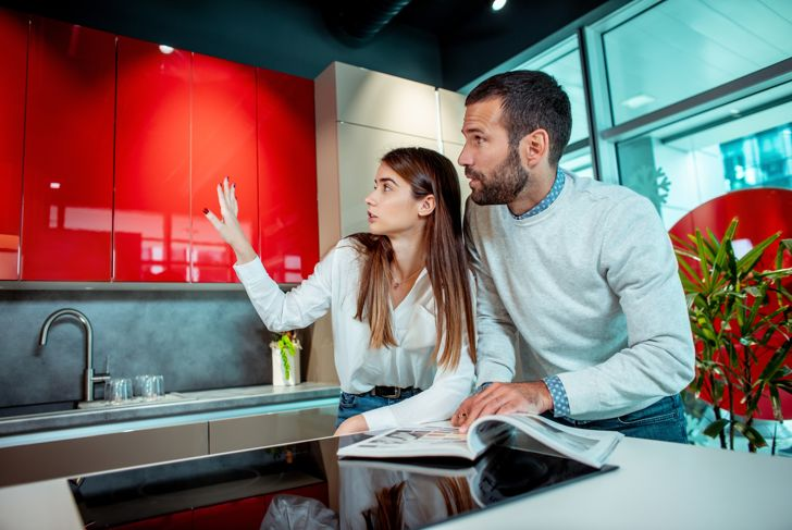 Young husband and wife making renovation plans in a kitchen department of a home improvement store. A woman is pointing at something to the man.