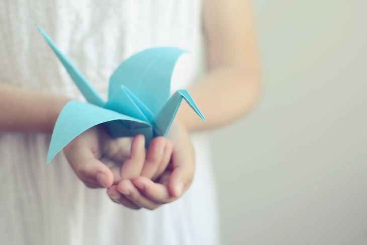 Little girl holding a blue origami bird in her hands