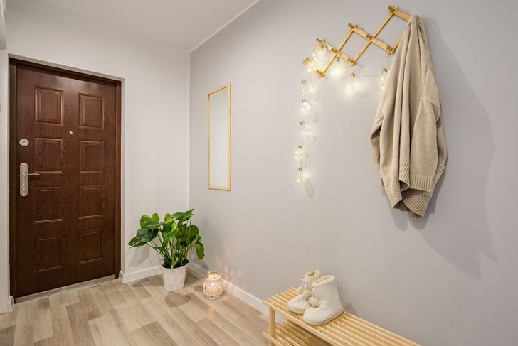 Simple entryway with gray walls, wooden door and shoe bench