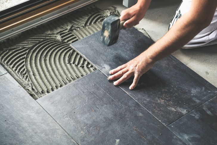 Worker carefully placing ceramic floor tiles on adhesive surface