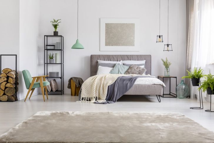 The upholstered bed frame, plush area rug, fluffy accent pillow, knit throw, glass jars, and plants illustrate how differing textiles make for interesting design.