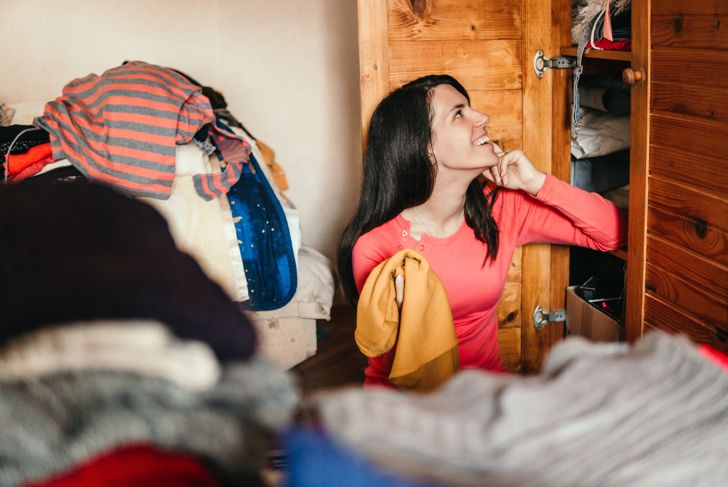 Young woman is sorting out wardrobe