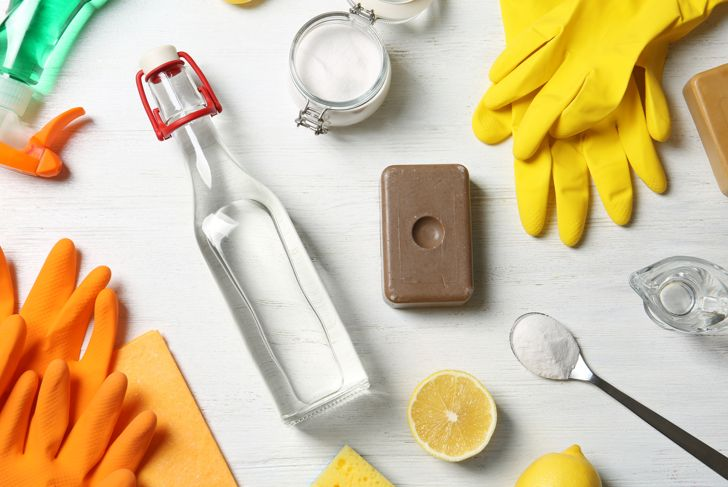 Flat lay composition with vinegar and cleaning supplies on white wooden background