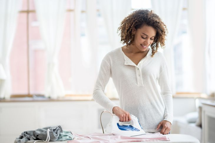 African American woman ironing clothes at home - house chores concepts