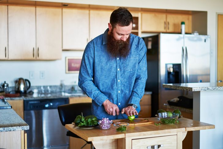 bearded man rolling limes for guacamole recipe in kitchen shot with natural light