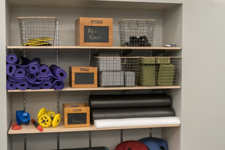 Shelf of work out equipment in modern gym. Yoga, classes, stretching.