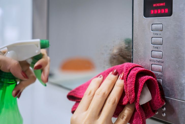 Close up of housemaid hands using a spray detergent to clean microwave in the kitchen.