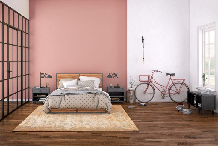 Bedroom with pink walls, a wooden bed, and a pink bike