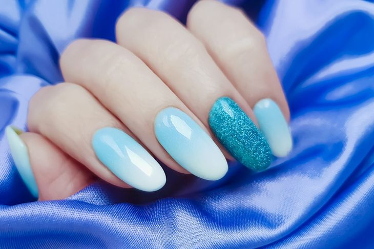 A blue ombre manicure accented with one glitter nail