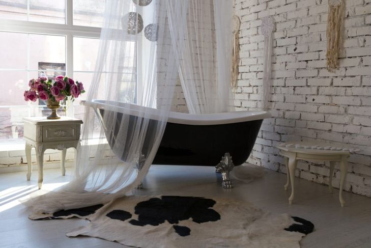 Several macramé wall hangings in a bathroom surrounding a claw-foot tub