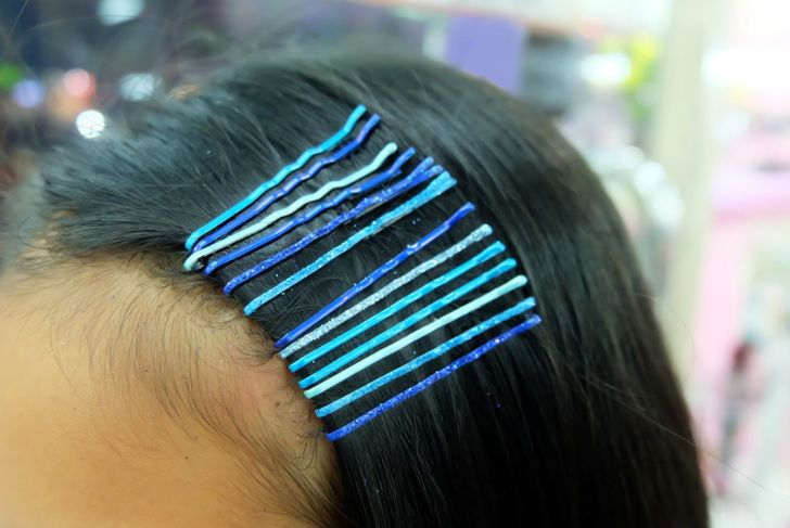 A female wearing several bobby pins in shades of blue