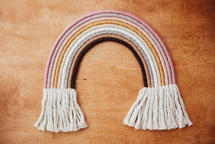 A macramé rainbow wall hanging against a wooden backdrop