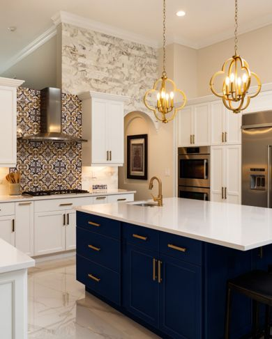 Interesting tile and the navy island make this white and gold kitchen memorable.