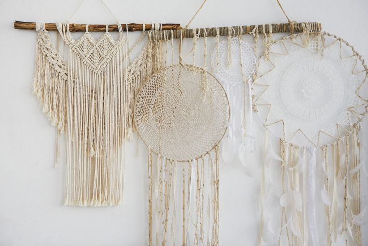 Several macramé hangings of different sizes clustered together on a wall