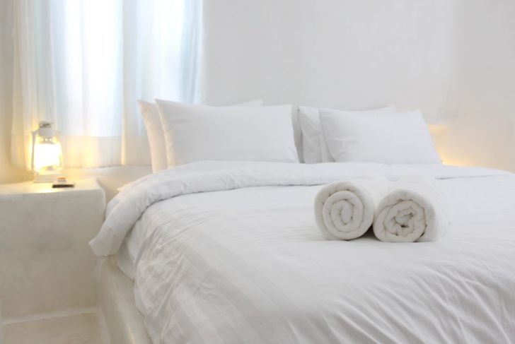 Bedroom with white walls, bed, and furniture