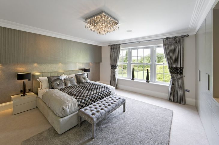 Glamorous bedroom with silver wallpaper and chandelier