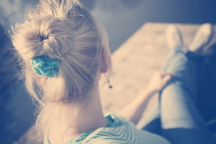 A woman wearing a topknot and a flower hair clip