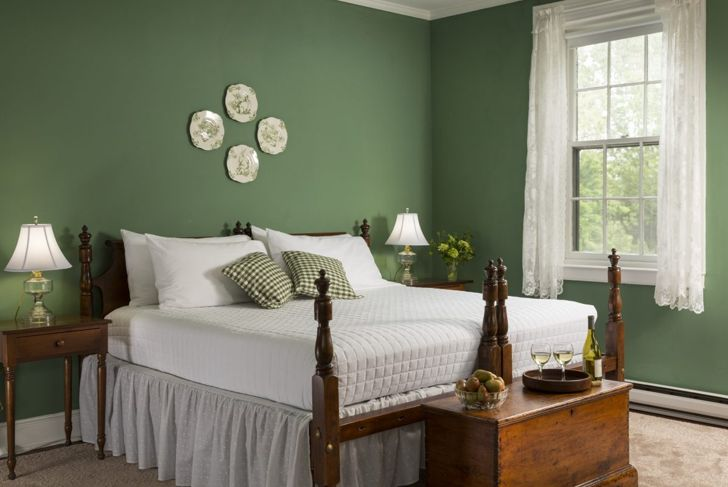 Bedroom with green walls and wooden bed